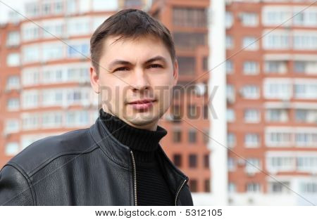 Young Man Against  Background Of  Building