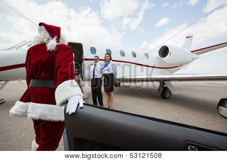 Santa disembarking car while walking towards private jet with pilot and airhostess standing by