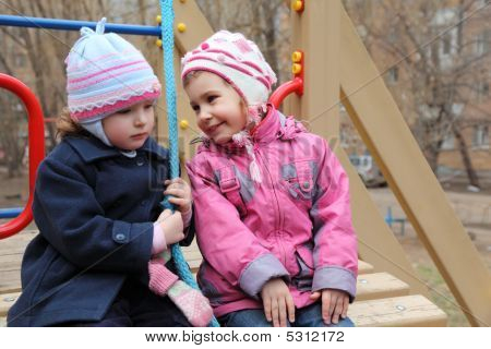 Two Girls Sit On Playground