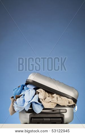 Suitcase Overflowing With Clothes
