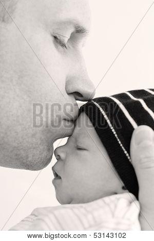Happy Father Kisses Newborn Son