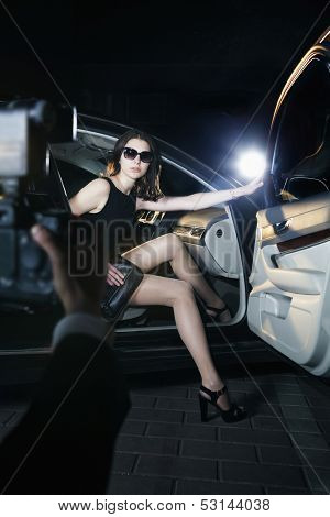 Paparazzi photographer taking photo of young beautiful woman stepping out of car