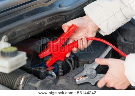 Hands connecting booster cables to a car battery
