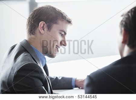 Two business people smiling and looking down at business meeting