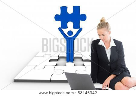 Composite image of blonde businesswoman using laptop