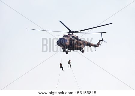 Two man climb from helicopter down a rope