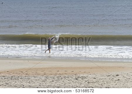 Man Throws A Fishing Net Into The Sea