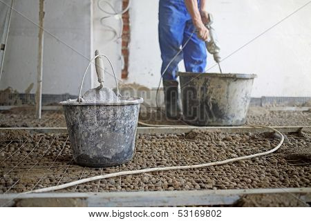 Room with expanded clay aggregate on the floor and worker with tool