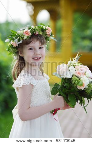 Little pretty girl in white dress and wreath holds bouquet outdoor.