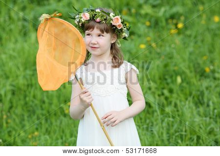 Little funny girl in white looks at butterfly sitting at net on green meadow.