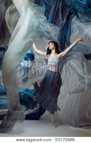 Beautiful fashion model dancing with blue fabrics.