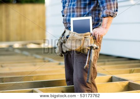 Midsection of construction worker with tablet computer and hammer in toolbelt at site