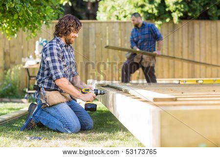 Manual worker drilling wood with coworker working in background at construction site