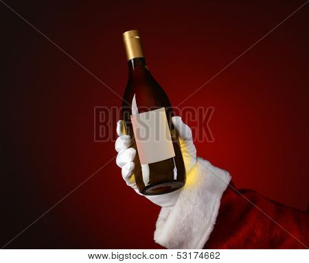 Closeup of Santa Claus holding a bottle of Chardonnay wine in his hand. Hand and arm only over a light to dark red spot background.