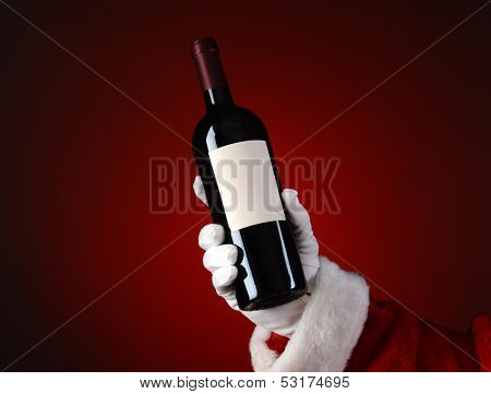 Closeup of Santa Claus holding a bottle of wine in his hand. Hand and arm only over a light to dark red spot background.
