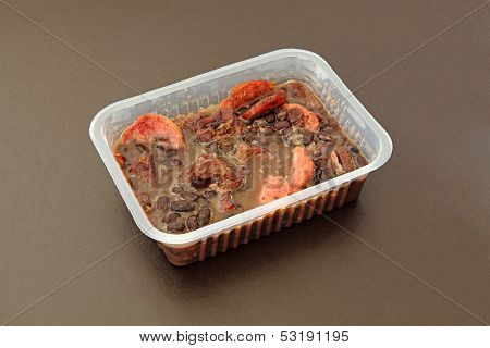 Brazilian Feijoada in a package for frozen food or to go. Package on a brown background.