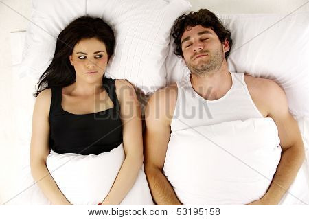 Man And Woman Laid In A White Bed