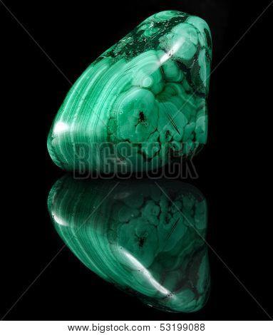 Polished malachite stone close up with reflection on black surface background
