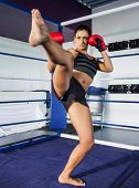 Full length of a pretty female boxer performing an air kick in the ring
