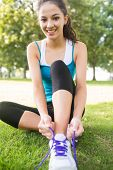 Active smiling brunette tying her shoelaces in a park on a sunny day