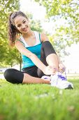 Cheerful active brunette tying her shoelaces in a park on a sunny day