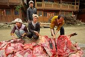 Asian Ax Cuts Carcass Of Pig On Rural Road.