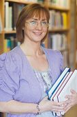 picture of librarian  - Female librarian posing holding some books smiling at camera - JPG