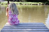 stock photo of dock a pond  - A little child sitting along on the river bank - JPG