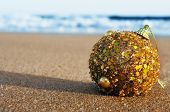stock photo of hemisphere  - a golden christmas ball on the sand of a beach - JPG