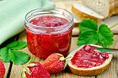 stock photo of strawberry  - Strawberry jam in a glass with leaves napkin knife on background wooden plank - JPG