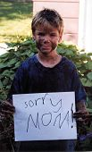 image of heartwarming  - a muddy boy holds a sign that reads  - JPG