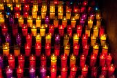 stock photo of praying  - Church candles in red and yellow transparent chandeliers - JPG