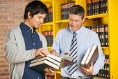 stock photo of librarian  - Happy male student holding books while discussing with librarian in college library - JPG