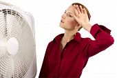 foto of heatwave  - businesswoman is cooling herself with an electric fan - JPG
