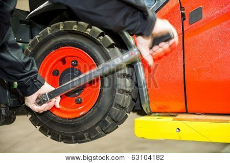 Maintenace on a forklift, a worker is changing the tyres.