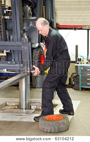 Forklift mechanic replacing a front tyre on a forklift in a workshop