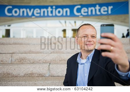 Business man taking a selfie with his smart phone in front of a convention center