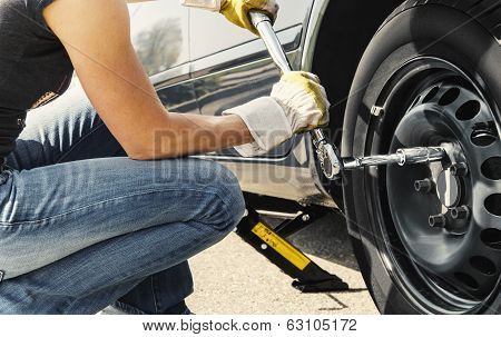 Woman Changing Tire Car