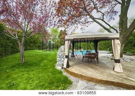 Backyard of residential house in spring with wooden deck and gazebo