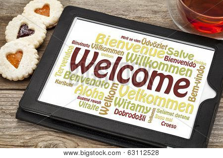 welcome word cloud in different languages on a digital tablet with a cup of tea and heart cookies