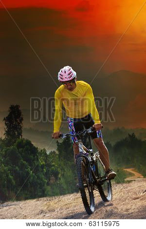 Young Man Riding Mountain Bike Bicycle Crossing Mountain Hill Jungle Track With Dusky Sky Scene Use