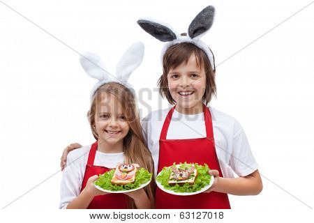Happy chefs with bunny ears holding rabbit shaped sandwiches - isolated