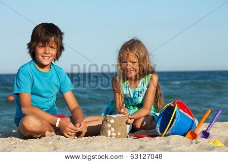 Kids playing in the sand - building castles together on the beach