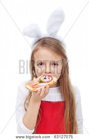 Little girl with bunny ears eating a sandwich decorated with a rabbit face - isolated