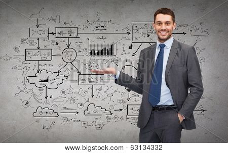 business, office, advertising and people concept - friendly young buisnessman showing big plan on concere wall