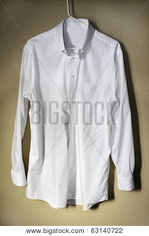Detail of white dress shirt hanging on hanger with light