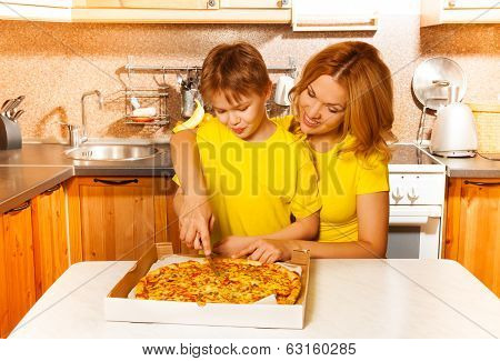 Boy and mother slicing pizza together in kitchen