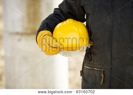 hand of worker with yellow hard-hat, selective focus