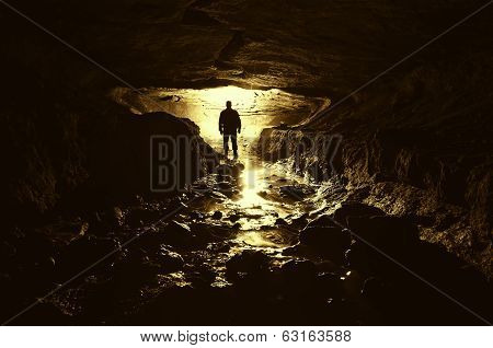 Man standing in a cave with light and underground river