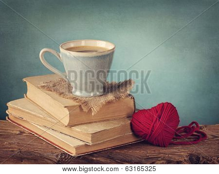 Cup of coffee standing on old books and wool heart